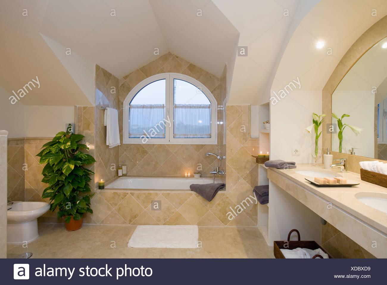 Unuual abuhardilladas arqueado sobre la bañera en el cuarto de baño ...
