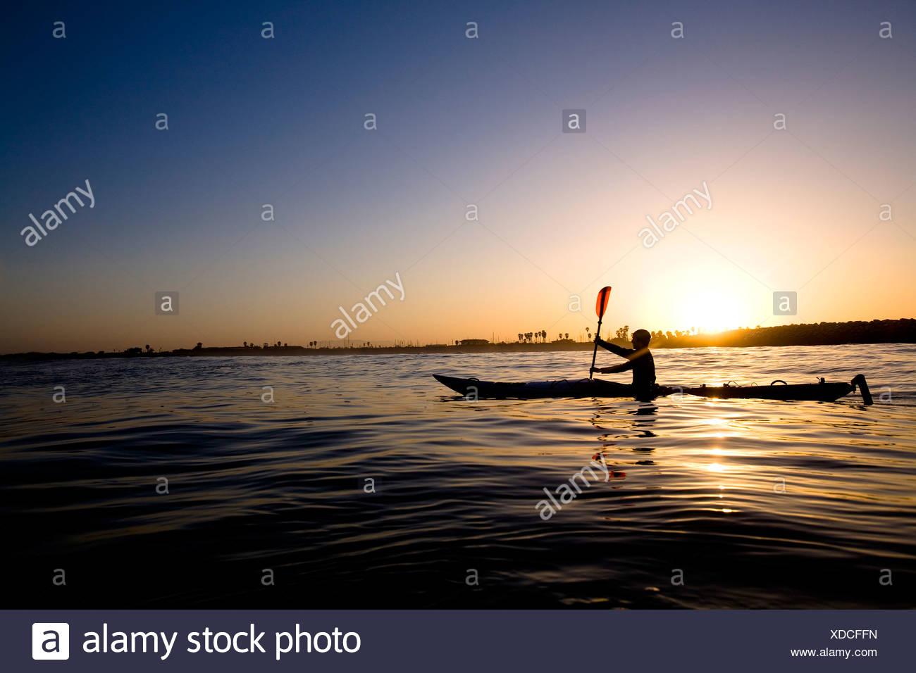 Una silueta joven remos un kayak de travesía, justo en las afueras de Ventura Harbor en Ventura, California. Imagen De Stock