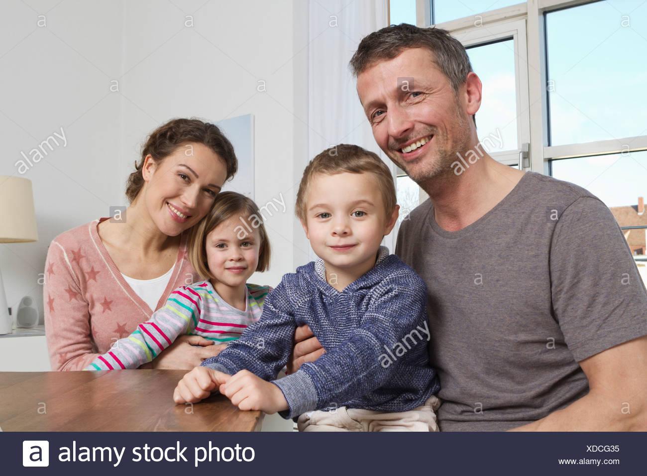 Sonriente, una familia de cuatro en casa Foto de stock