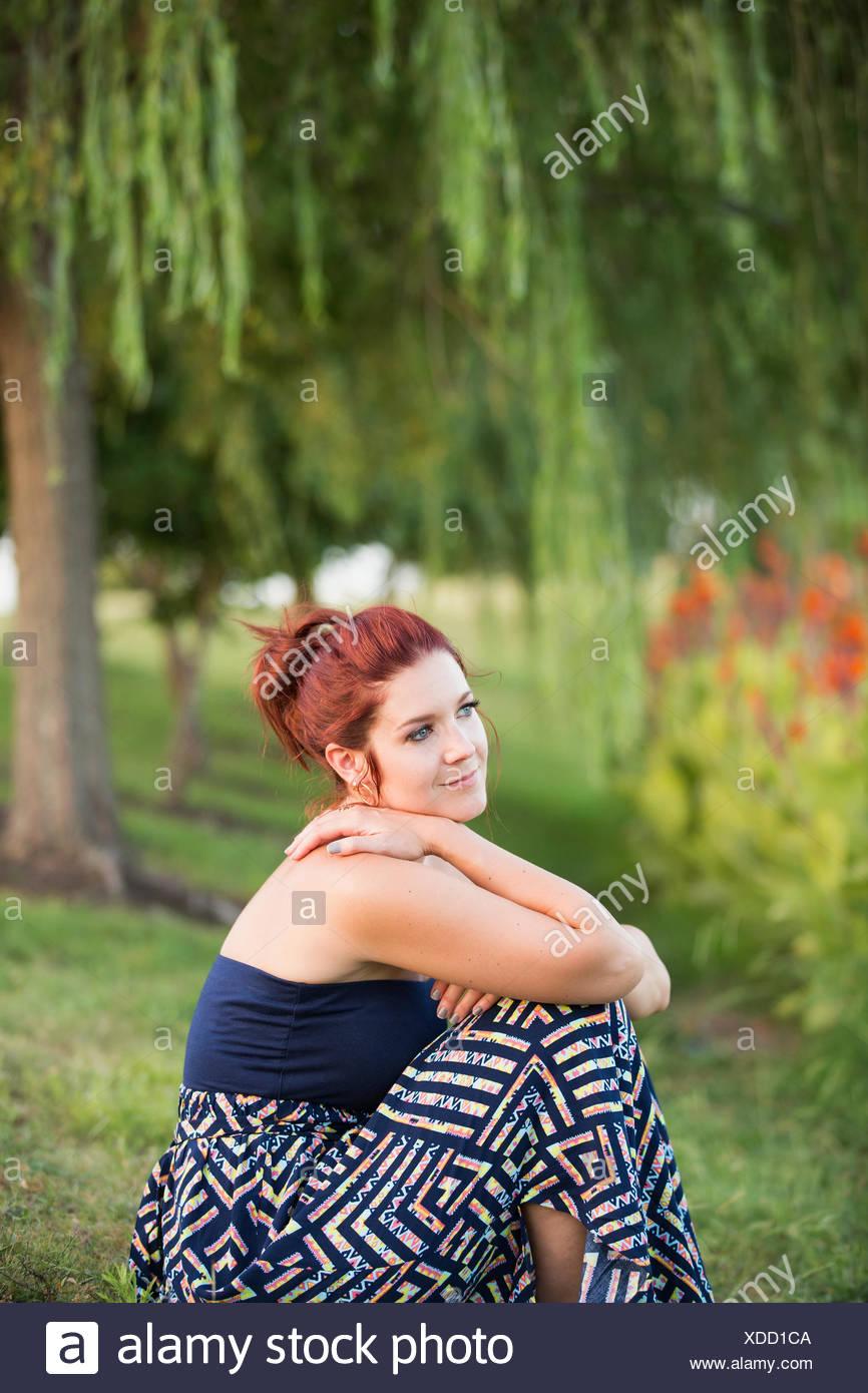 Una mujer sentada bajo un árbol de sauce llorón. Imagen De Stock