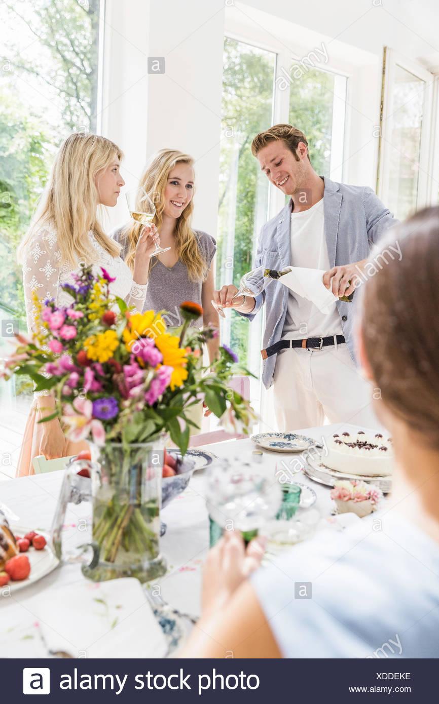 Joven vertiendo el champán para familia en fiesta de cumpleaños Imagen De Stock