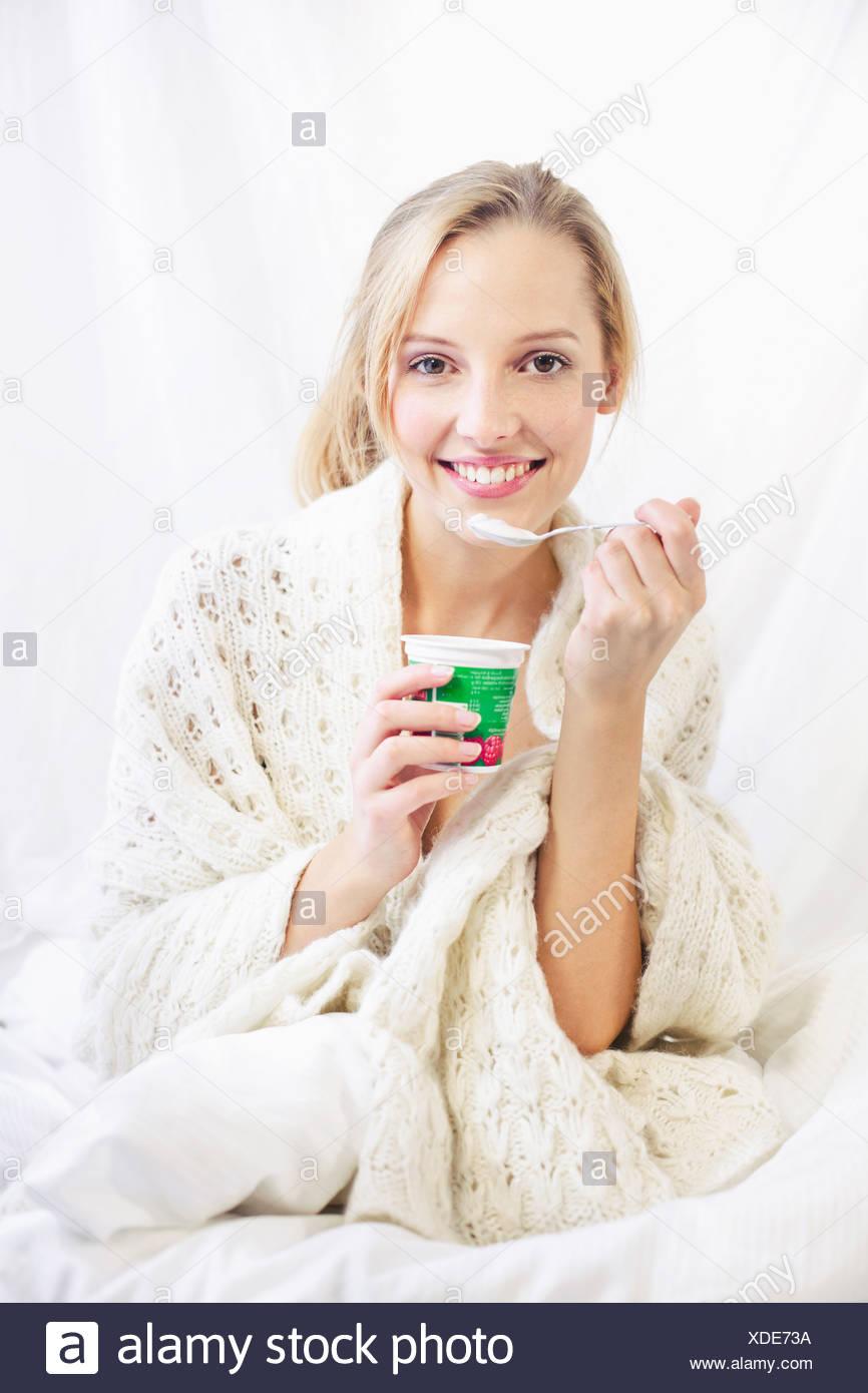 Mujer joven comer yogurt, sonriendo Imagen De Stock