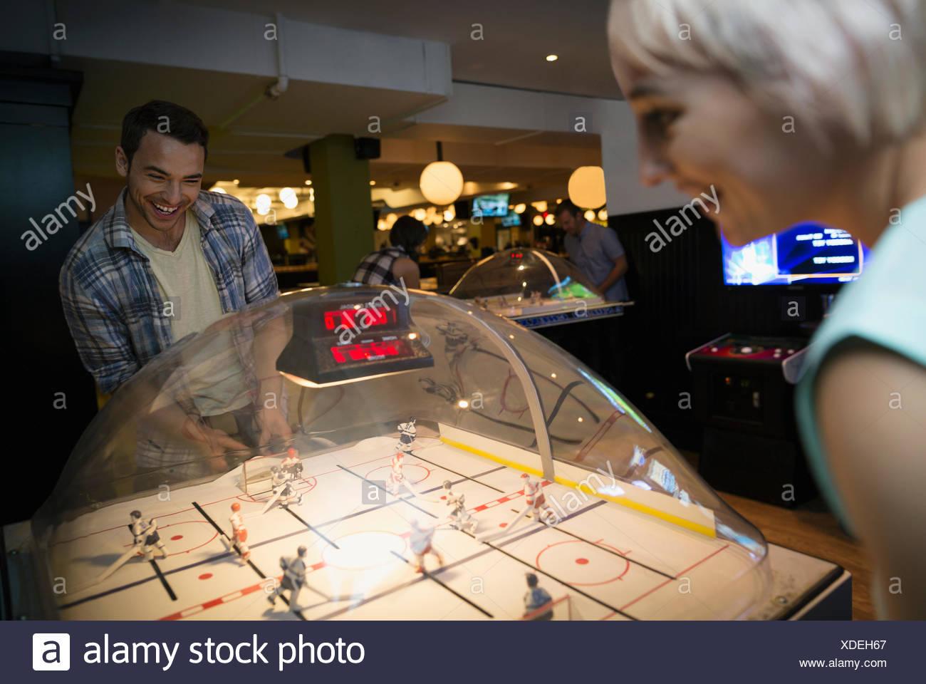 Amigos jugando bubble juego de hockey en el bowling alley Imagen De Stock