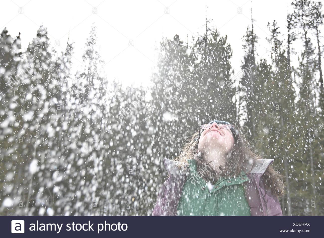 Mujer en la nieve lanzando su cabeza hacia atrás y riendo Imagen De Stock