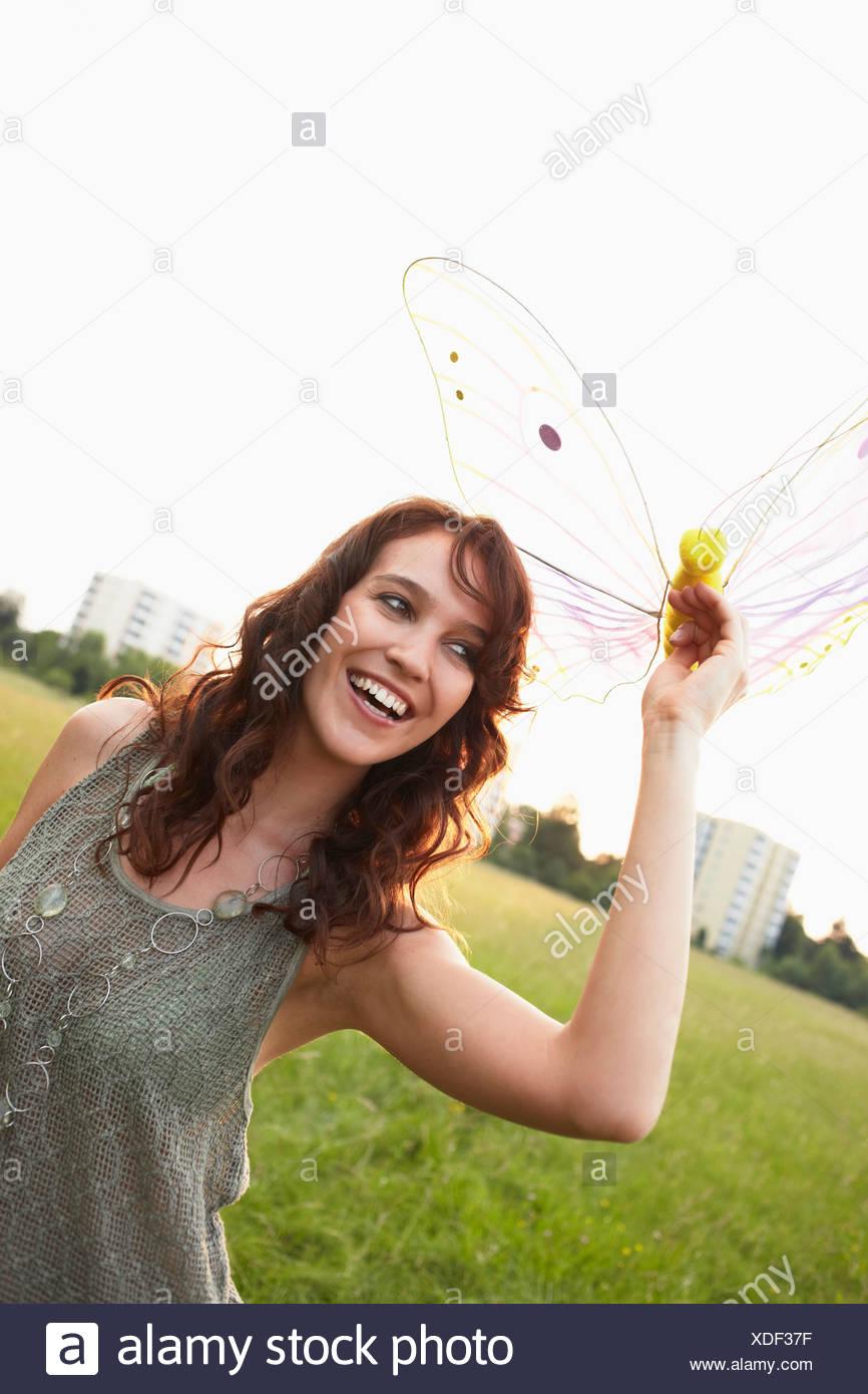 Mujer sosteniendo cerca de mariposas de juguete Foto de stock