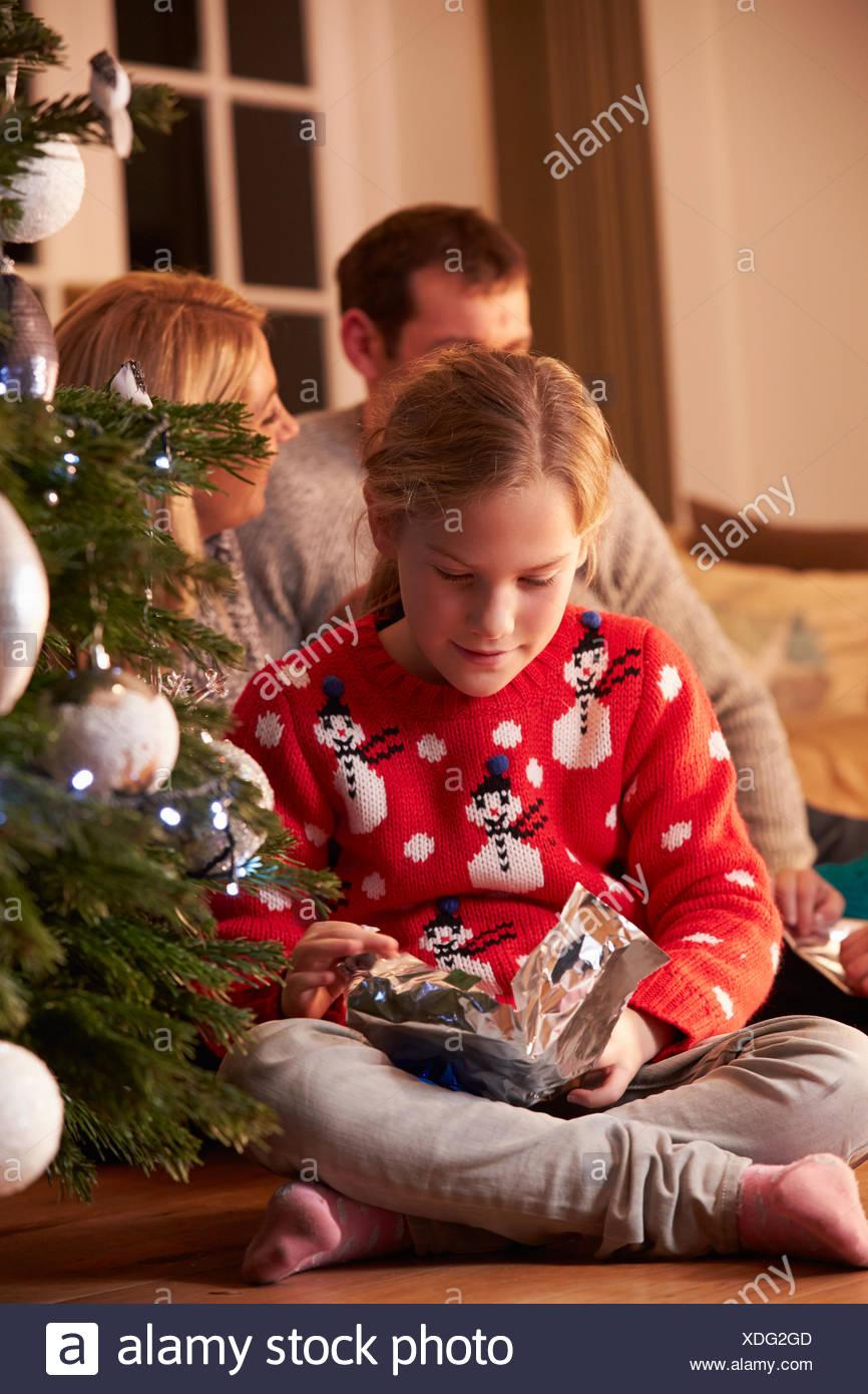 Chica desenvolviendo regalos por árbol de Navidad Imagen De Stock