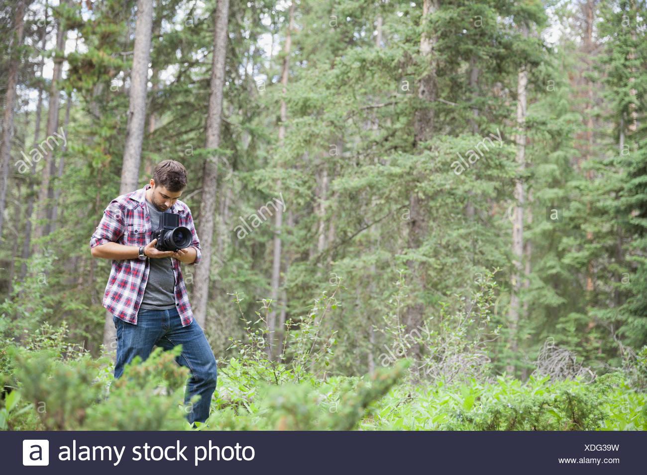 Fotógrafo macho usando una cámara SLR afuera Imagen De Stock