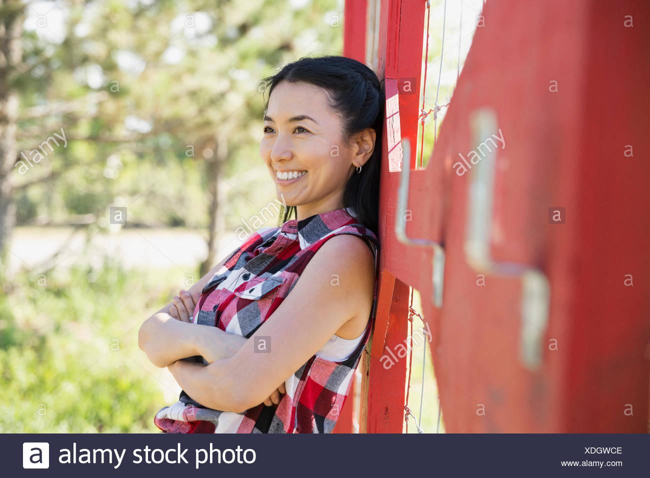 Mujer sonriente apoyándose en el cerco en el jardín Imagen De Stock