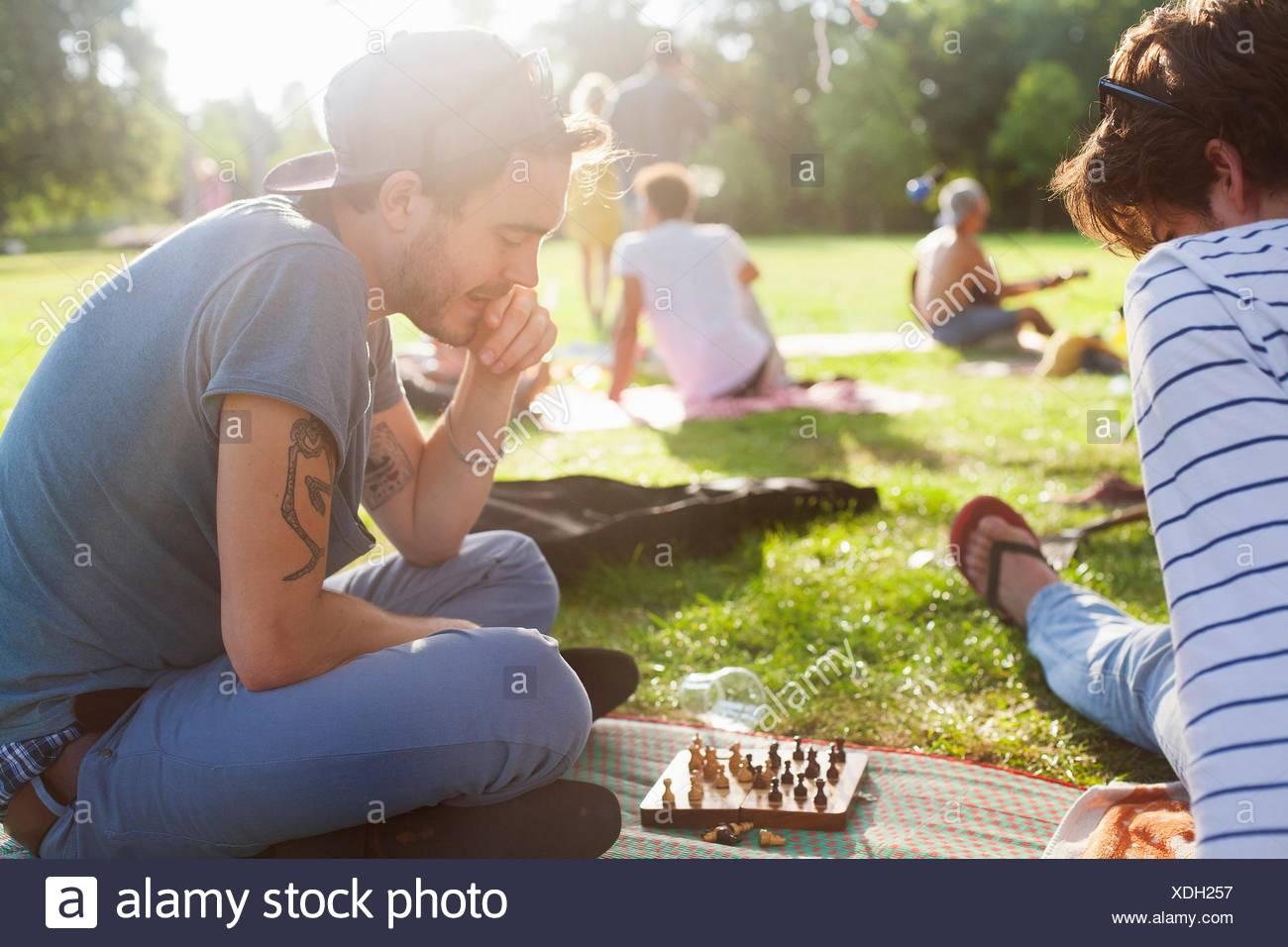 Los jóvenes adultos que juegan juegos de tablero en sunset fiesta en park Imagen De Stock