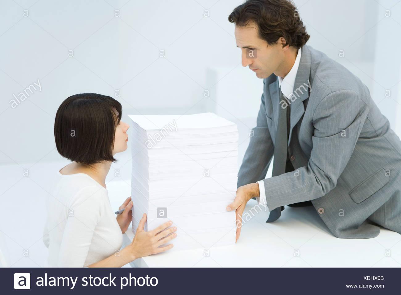 Boss empuje la pila de papel a través de escritorio a su ayudante Imagen De Stock