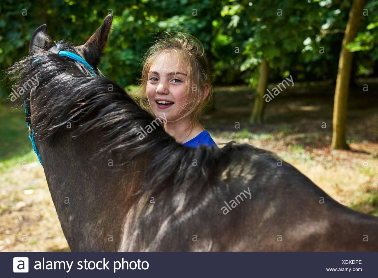 La cabeza y los hombros de la chica con el Caballo sonriente mirando a la cámara Imagen De Stock
