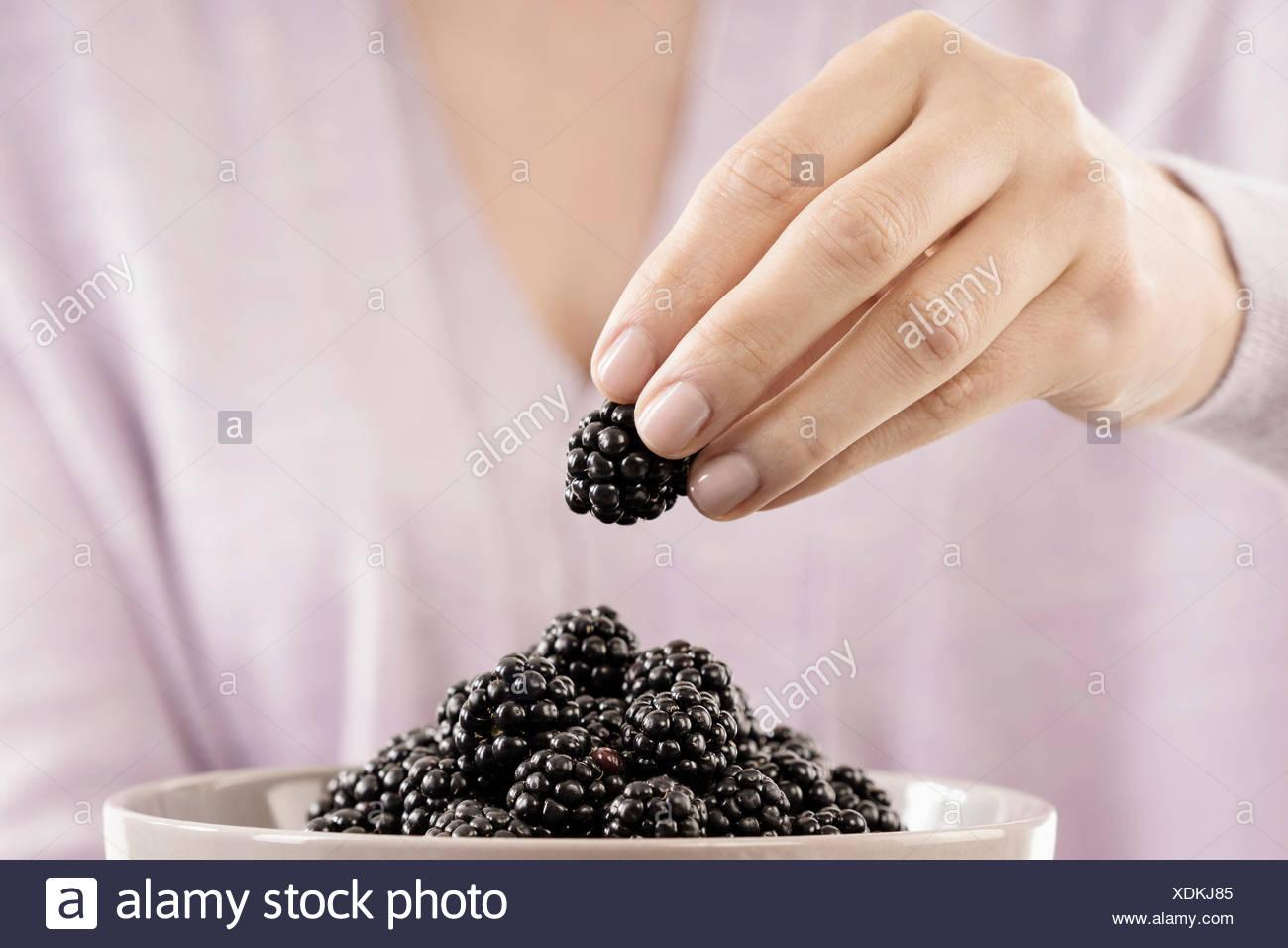 Vista de la sección intermedia de la mujer comer blackberry, Baviera, Alemania Imagen De Stock