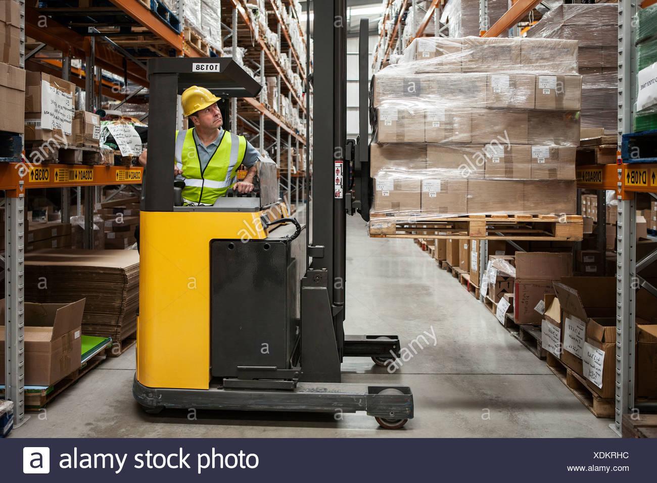 Hombre de transportar las existencias en almacén de distribución Imagen De Stock