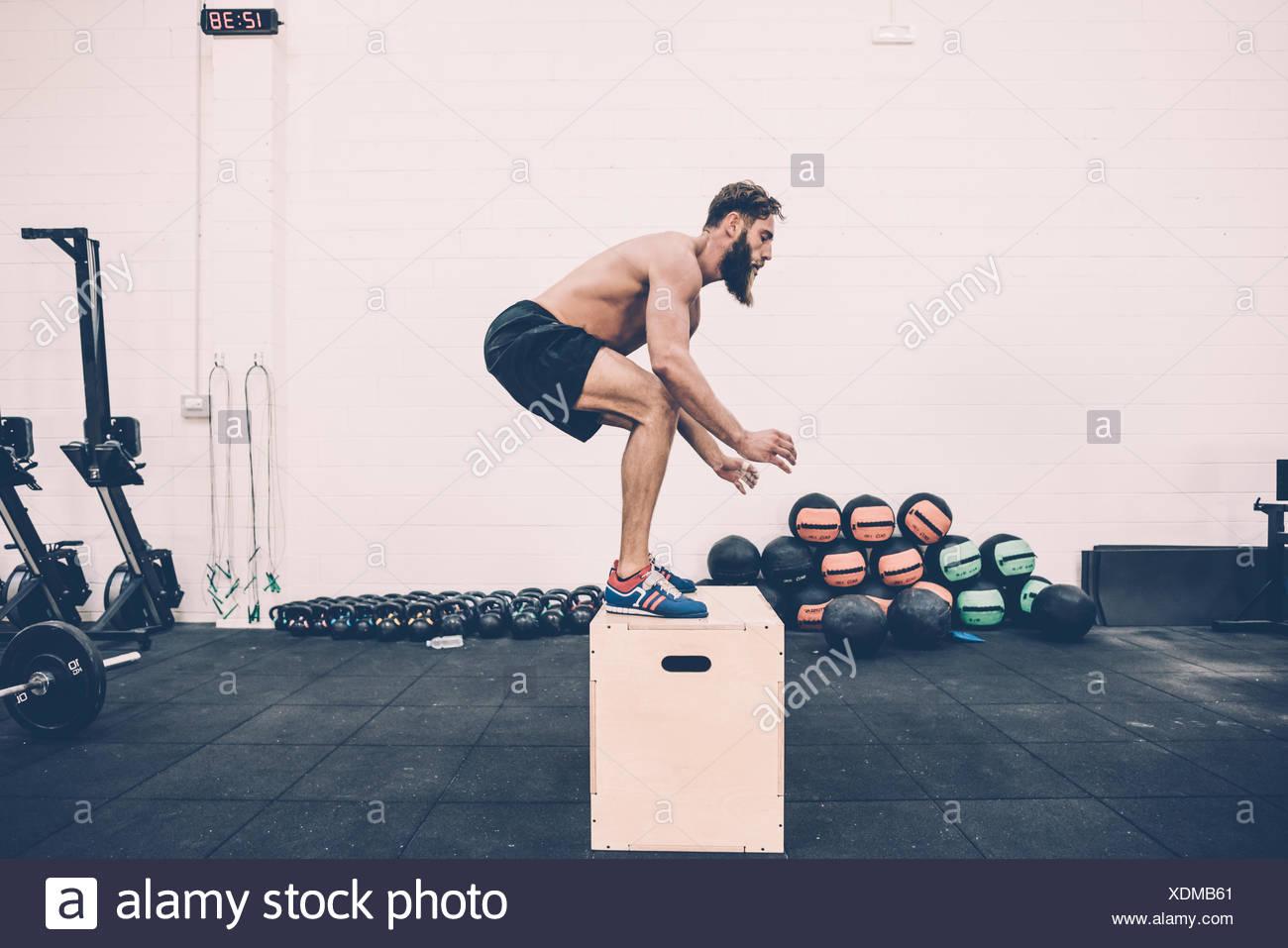 Macho joven entrenador de cross saltando sobre verificación en el gimnasio Imagen De Stock