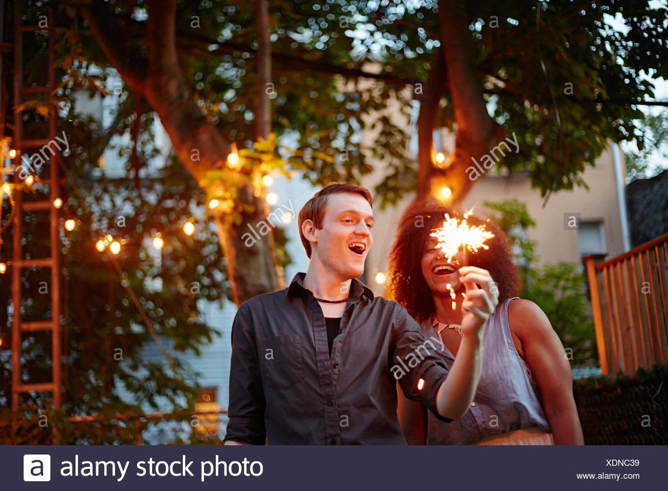 Joven la celebración de bengala en garden party Imagen De Stock