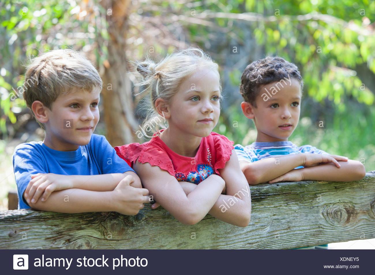 Tres hijos inclinarse sobre fence Mirar lejos Imagen De Stock