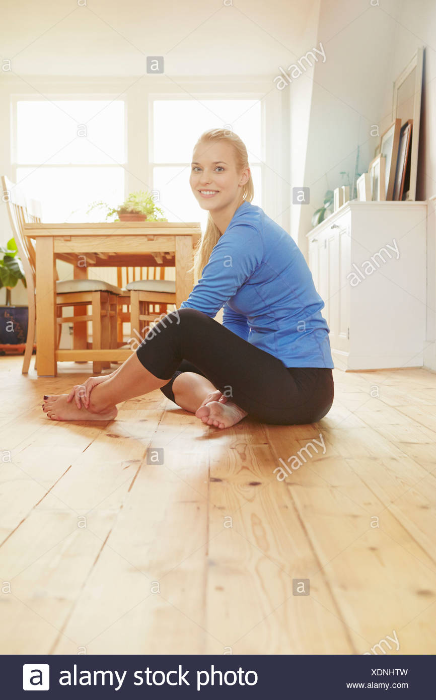 Mujer joven sentada en el suelo vistiendo ropa deportiva Imagen De Stock