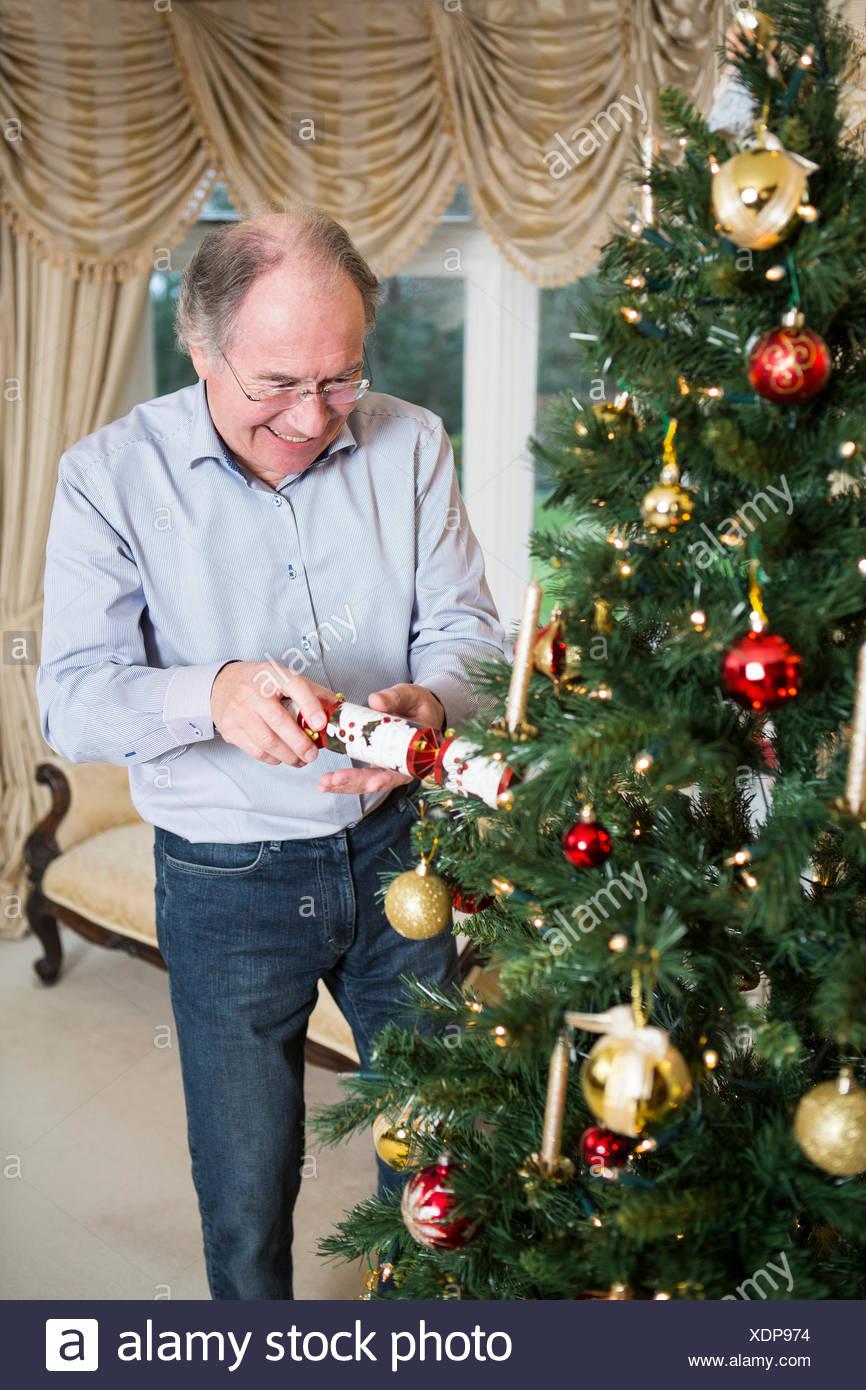 Hombre Senior apertura cracker de Navidad por árbol de Navidad Imagen De Stock