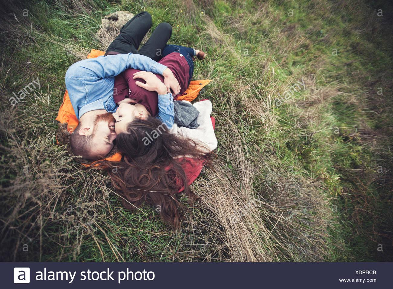 Pareja joven acostado sobre la hierba y abrazando Imagen De Stock