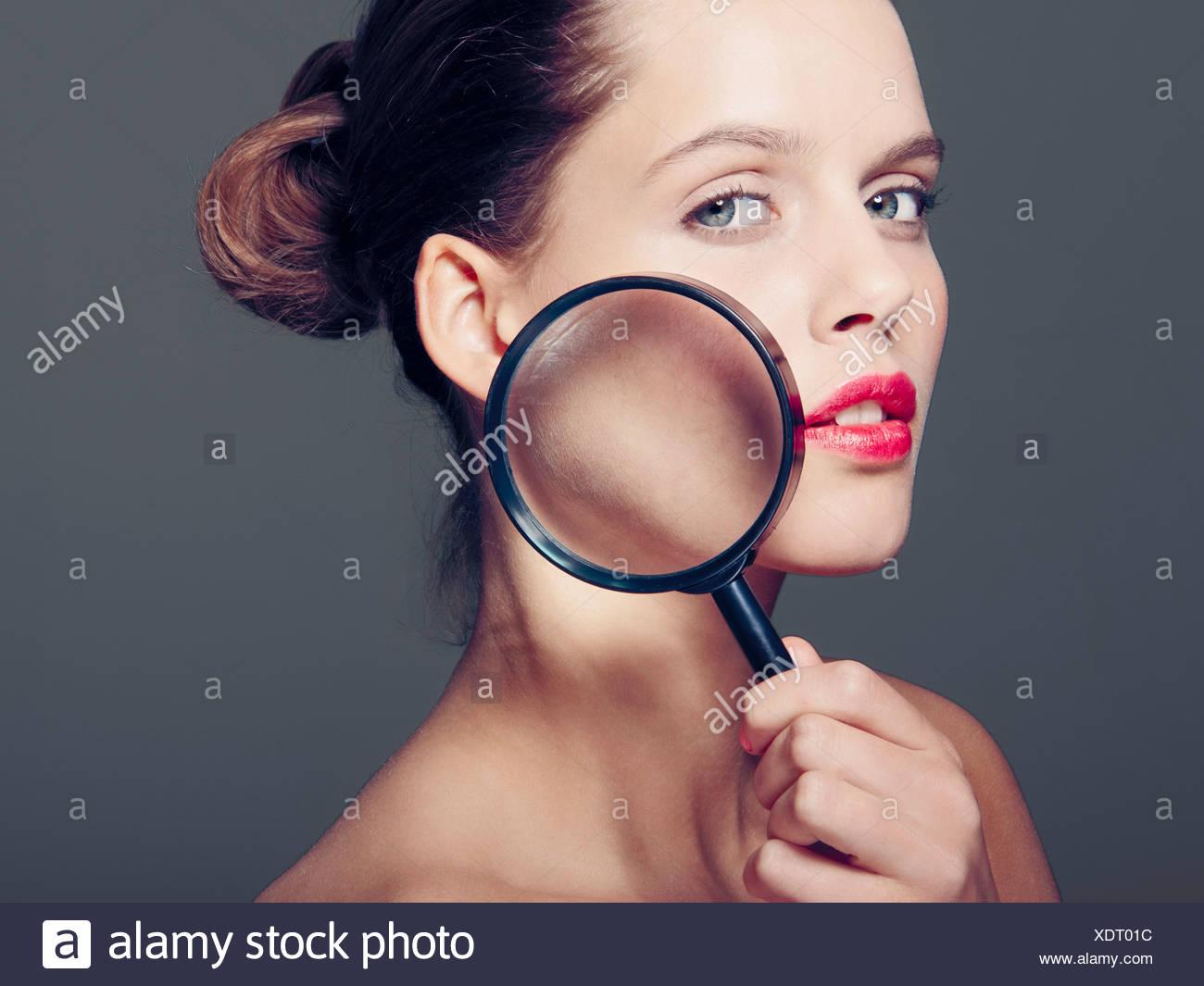 Mujer sosteniendo la lupa a cara Foto de stock