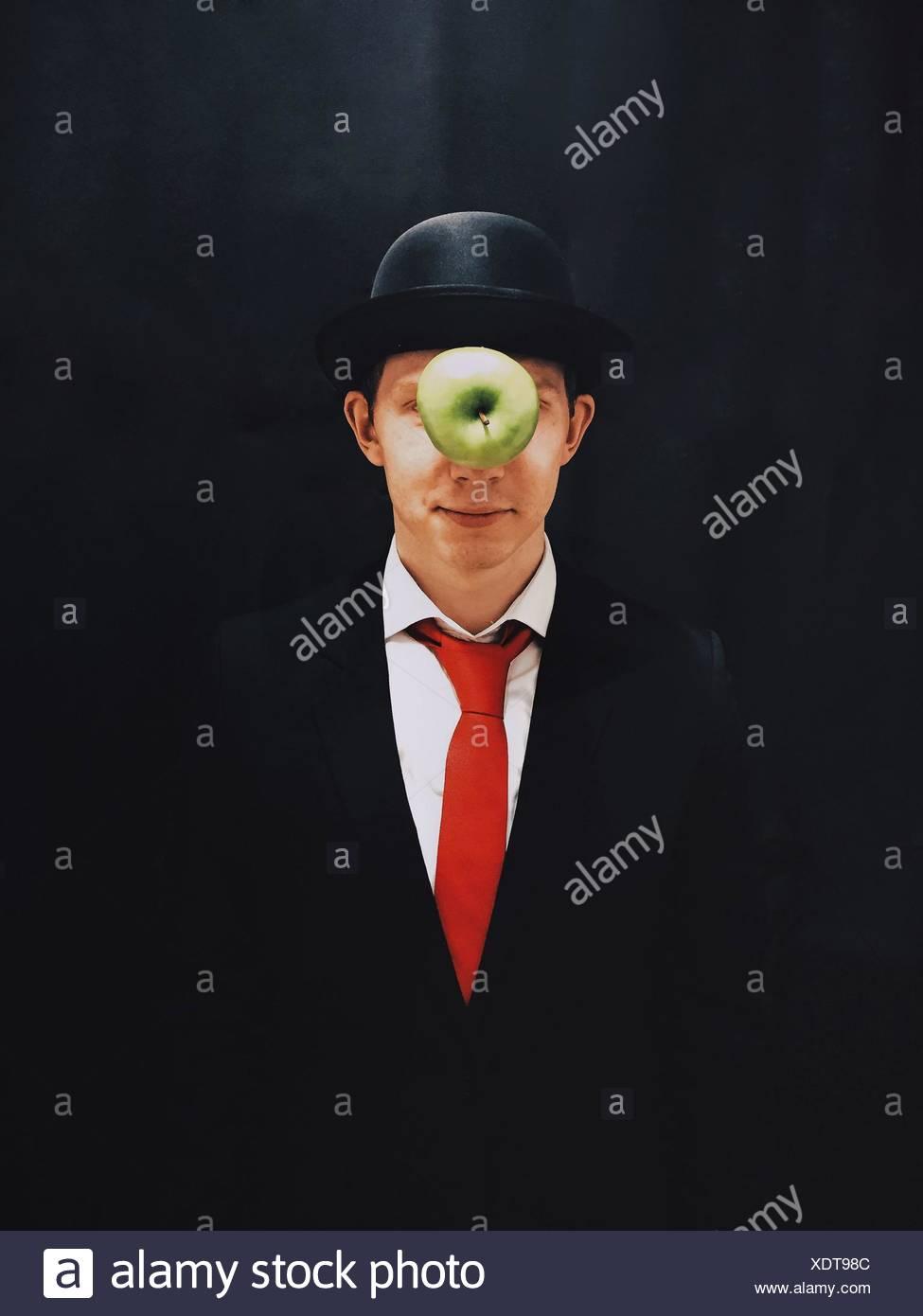 Apple en Mid-Air delante del hombre con sombrero contra el fondo negro Imagen De Stock