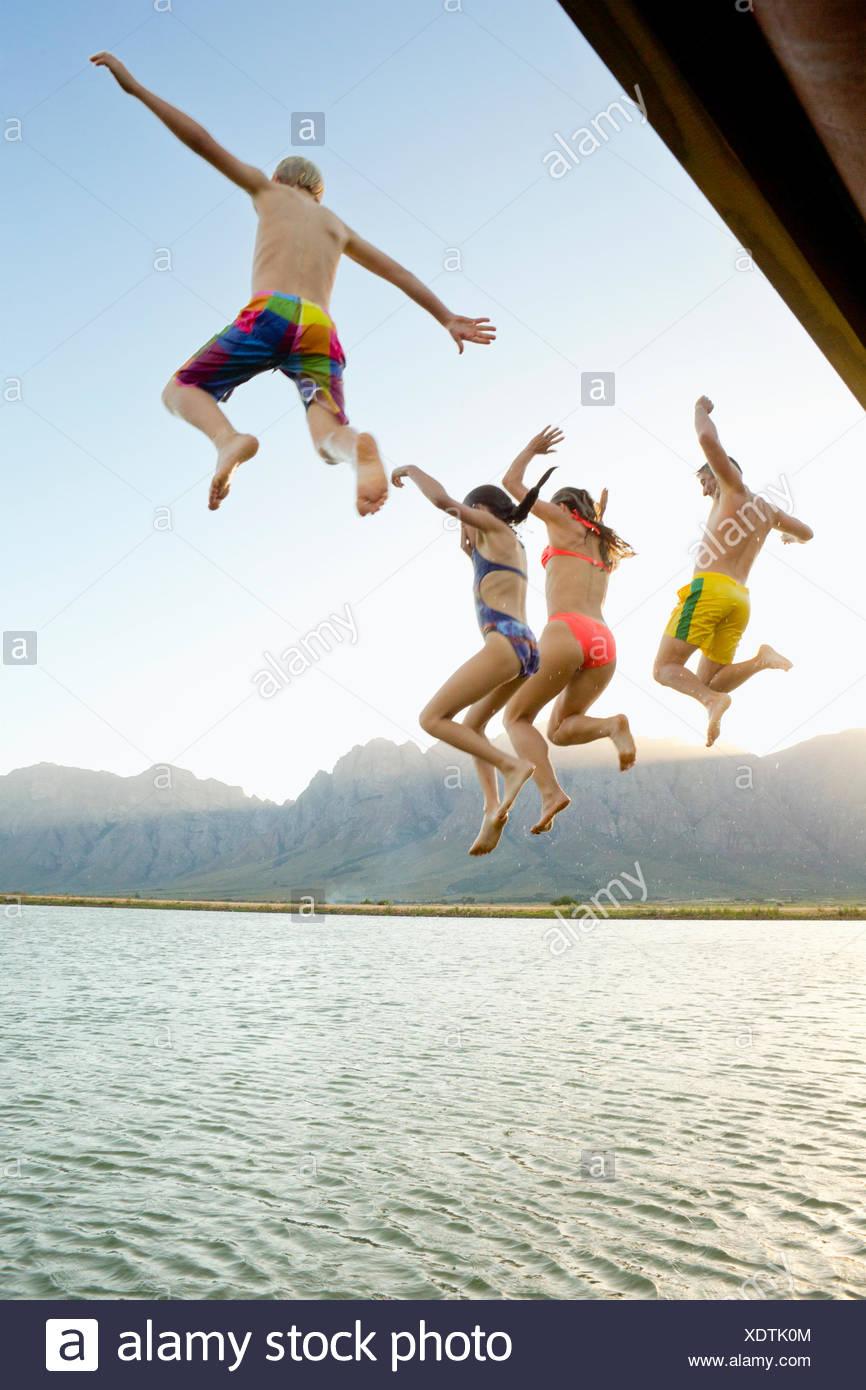 La familia, en traje de baño, saltando a un lago desde un embarcadero Imagen De Stock