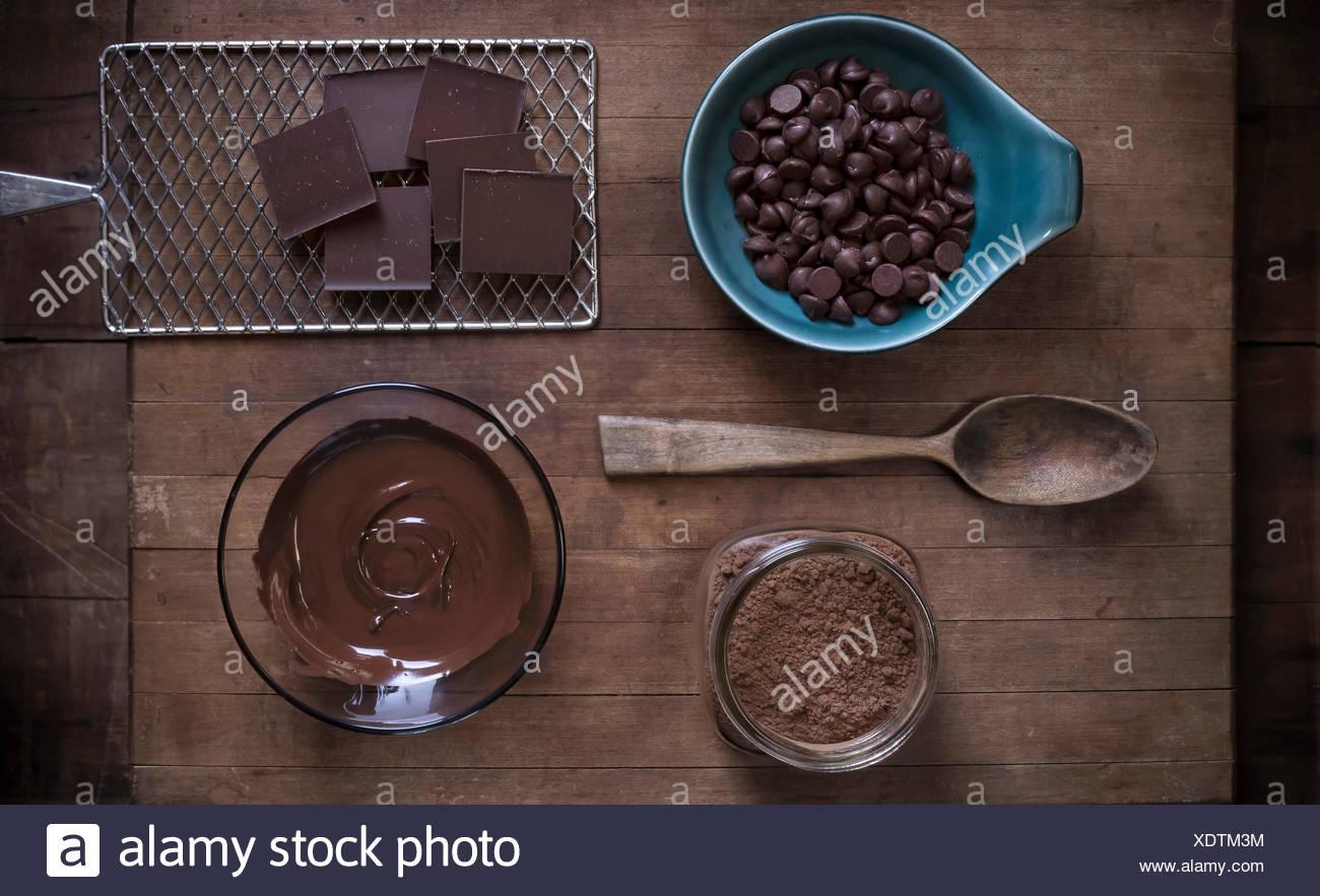 Vista superior de suministros para hornear chocolate dispuestos sobre una superficie de madera rústica con muebles antiguos de props. Imagen De Stock