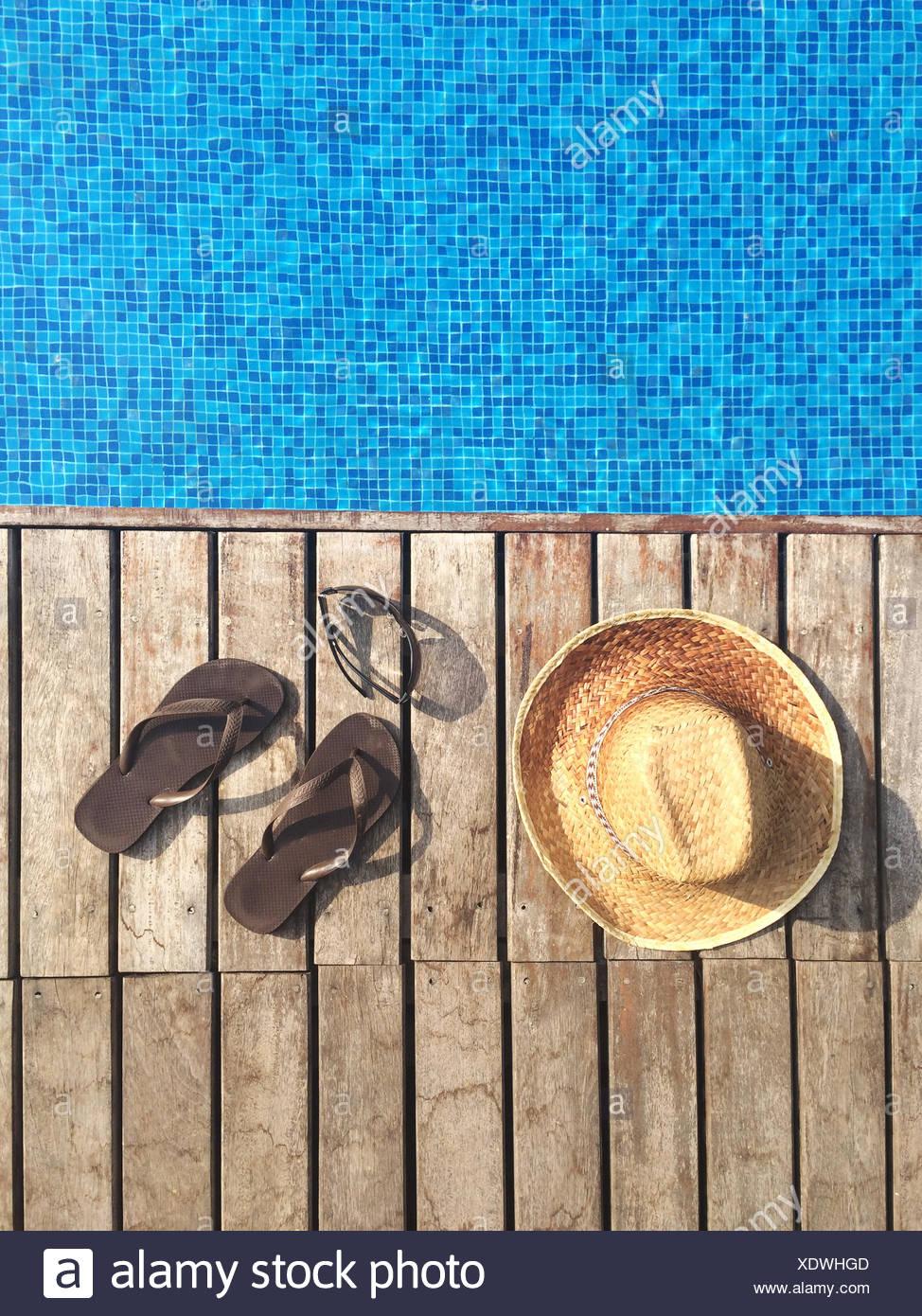 Sombrero para el sol, sandalias y gafas de sol con piscina Foto de stock