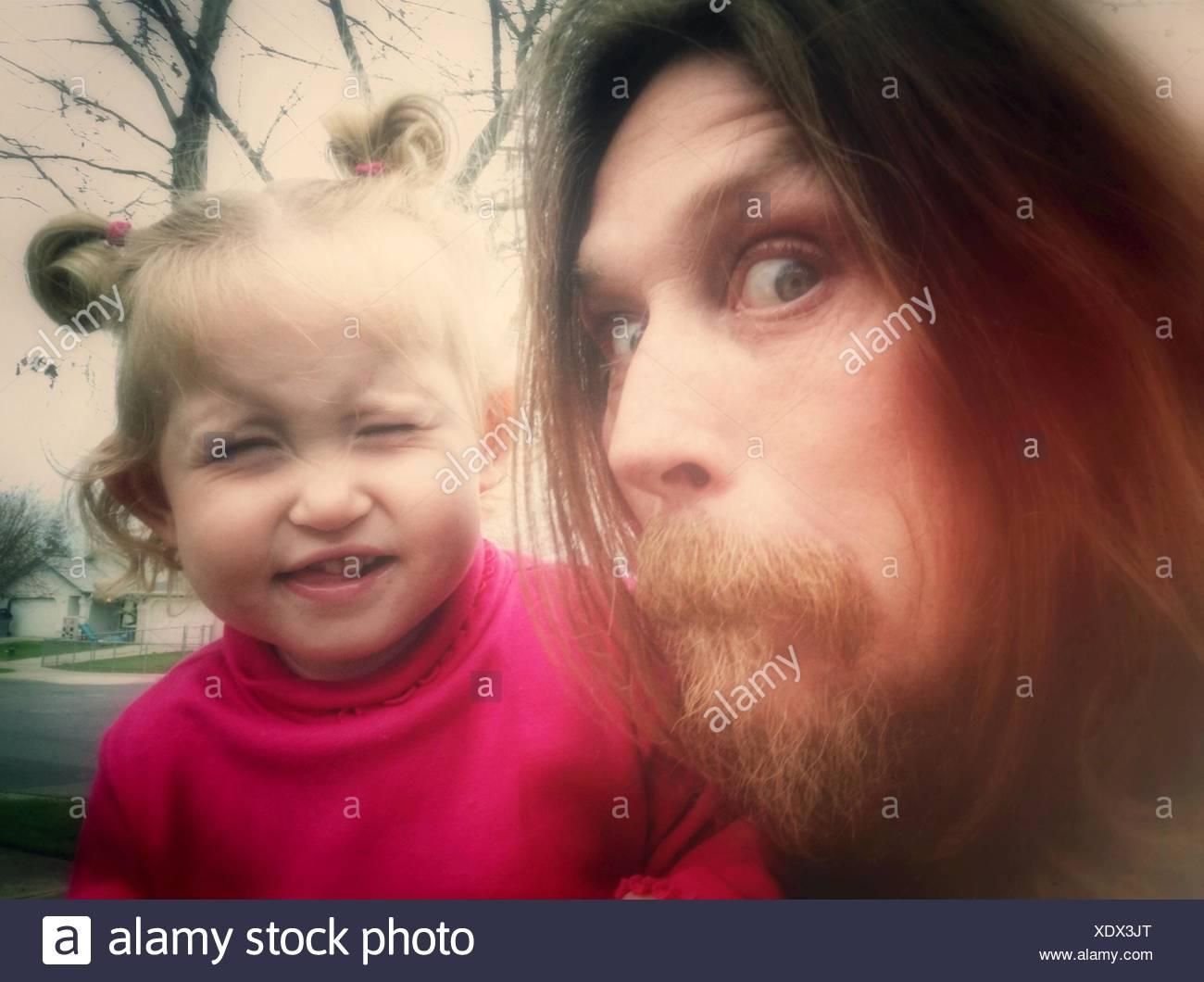 En primer plano el retrato de un hombre y de una niña haciendo caras Foto de stock
