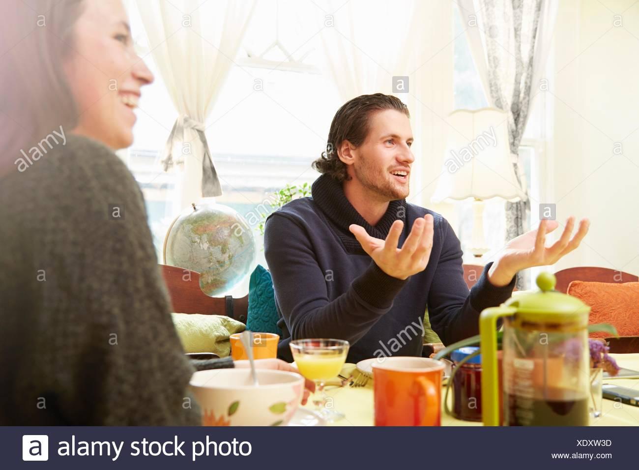 Vista sobre el hombro del joven, explicar con mesa de desayuno Foto de stock