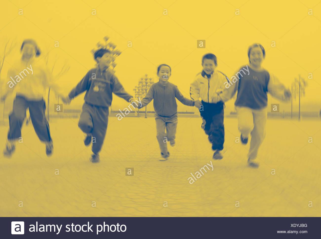 Niños corriendo de la mano en el patio de la escuela Imagen De Stock