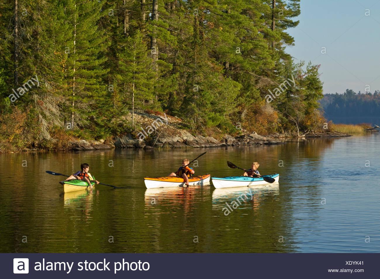 Tres jóvenes remar kayaks en el lago de origen, Algonquin Park ,en Ontario, Canadá. Imagen De Stock