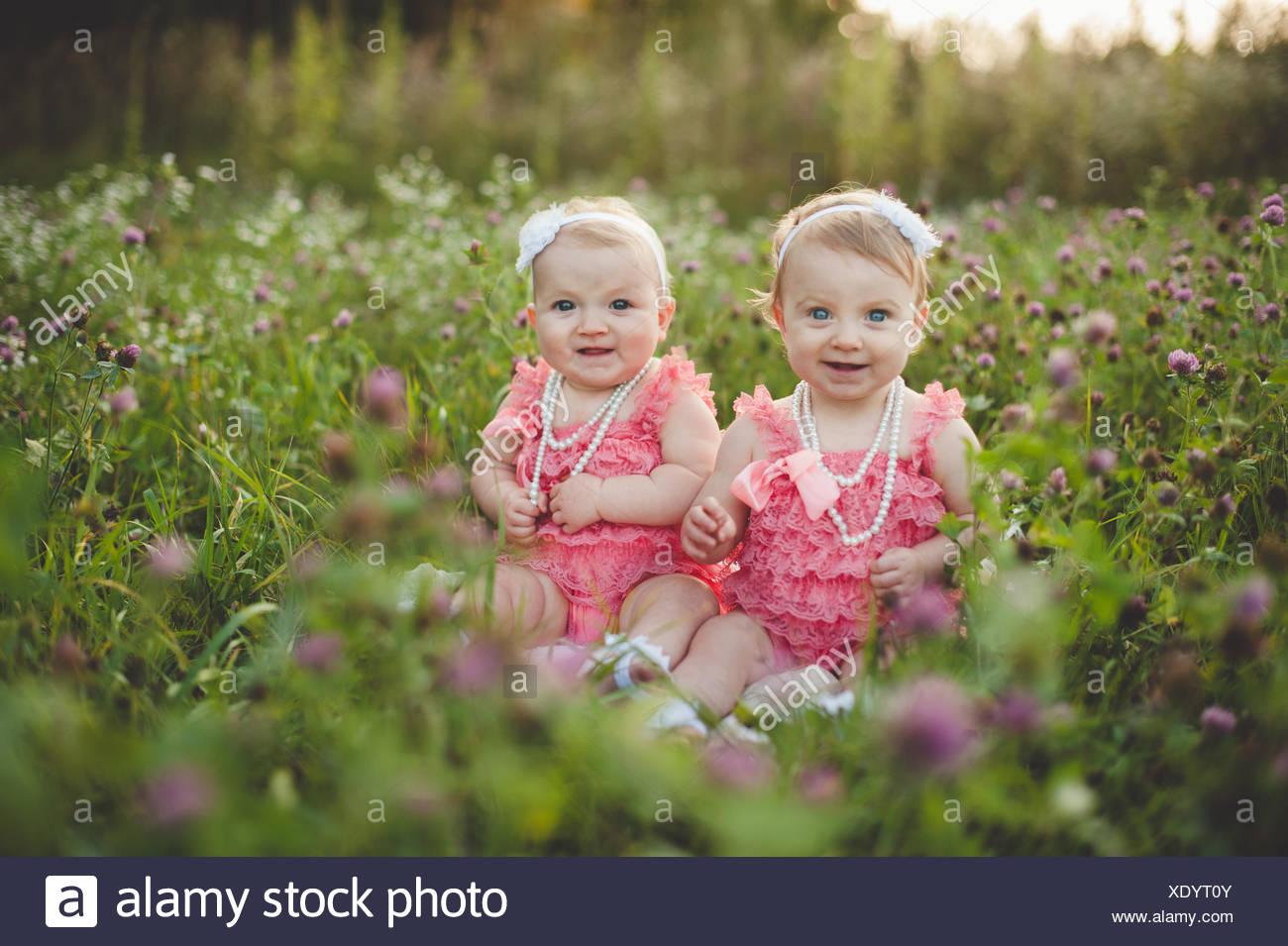 Retrato de hermanas gemelas bebé sentado en flor salvaje pradera luciendo vestidos rosa Imagen De Stock