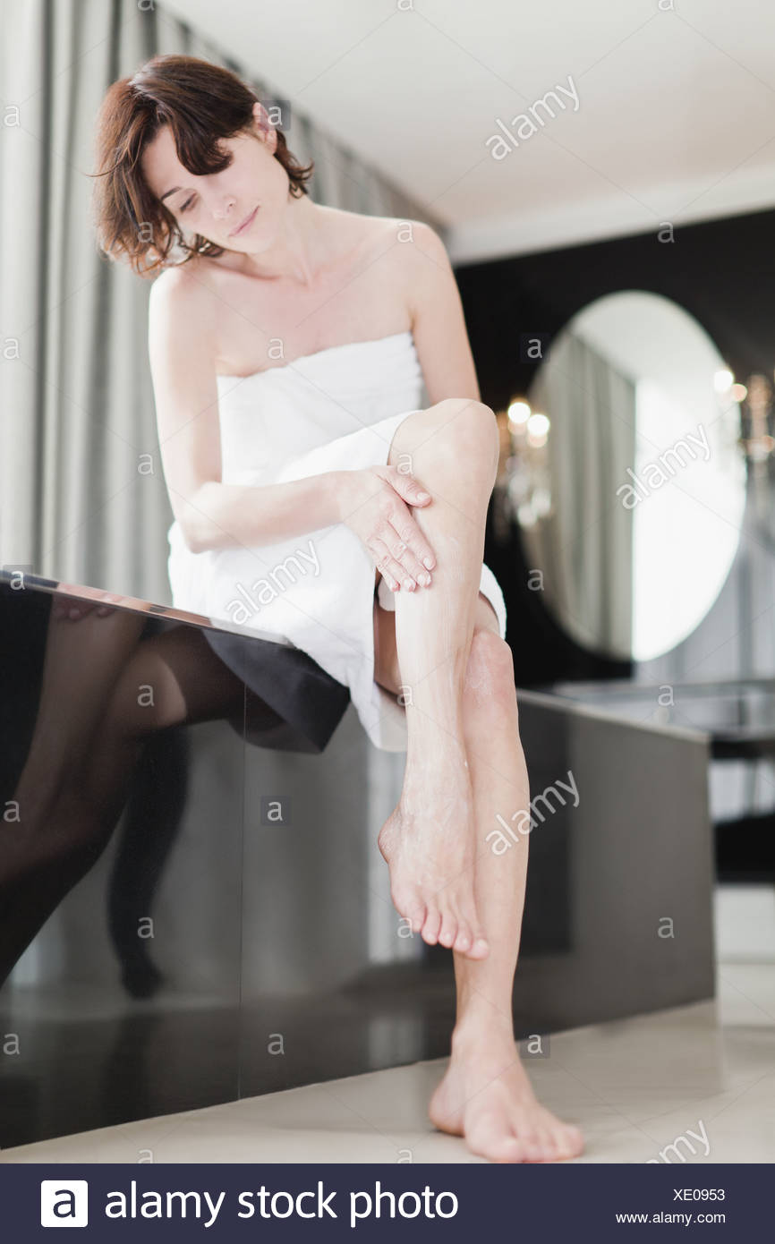 Mujer frota loción en las piernas Foto de stock