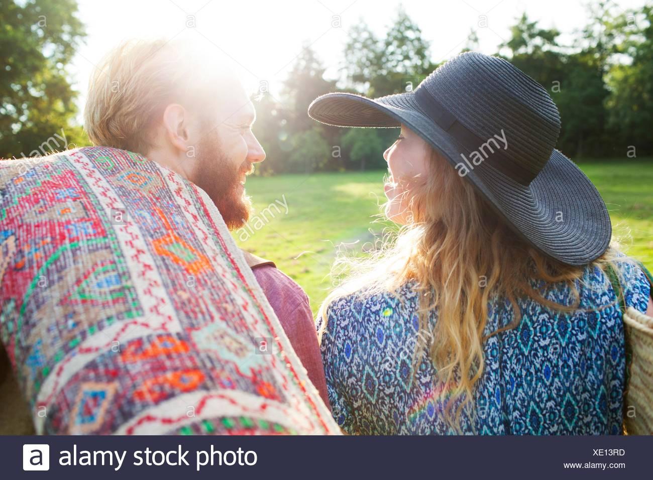 Vista trasera de la romántica pareja joven llevando la manta para picnic en el parque Foto de stock
