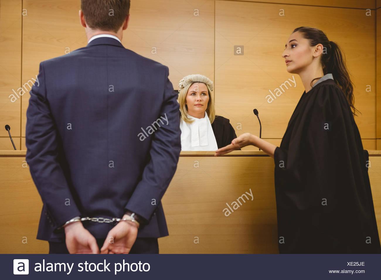 Abogado hablando con el criminal en esposas Foto de stock