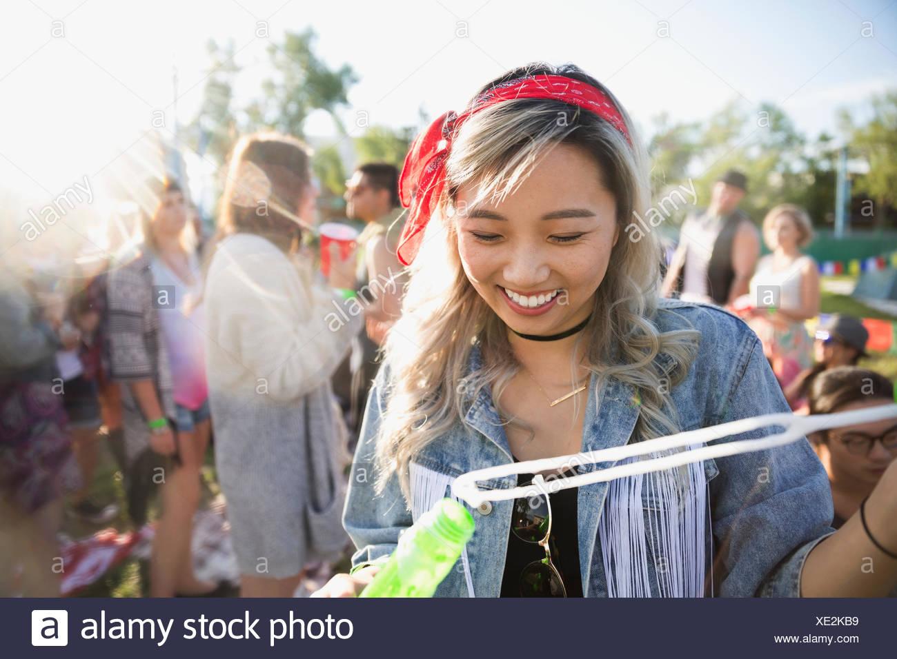Mujer sonriente soplando burbujas en el festival de música de verano Imagen De Stock