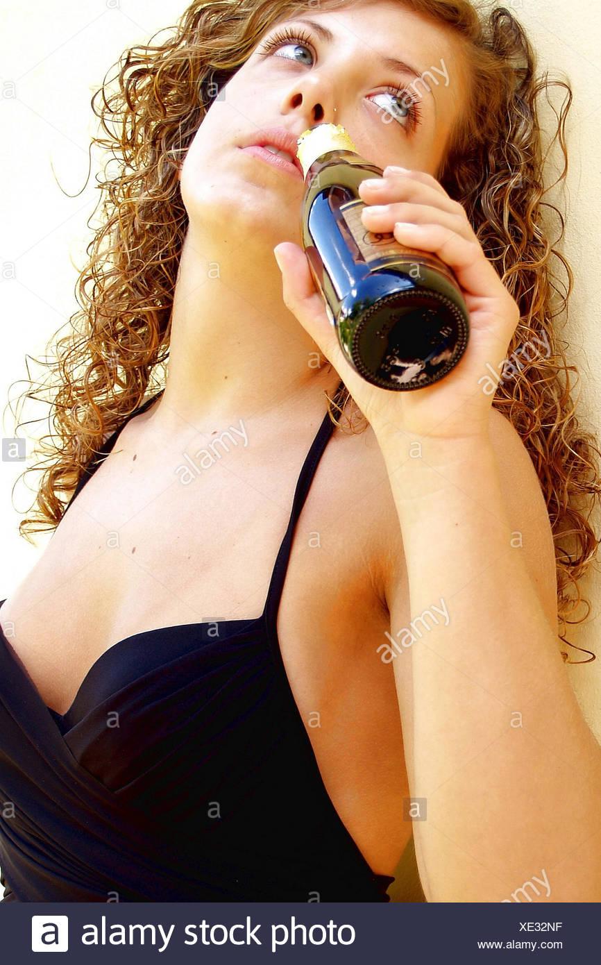 Mujer mirando hacia arriba cuidadosamente intentando ahogar sus recuerdos en el vino que está bebiendo de la botella Foto de stock