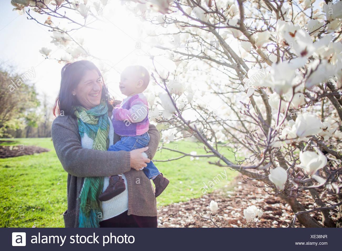 Retrato de una niña y su abuela junto a flor de magnolia. Imagen De Stock