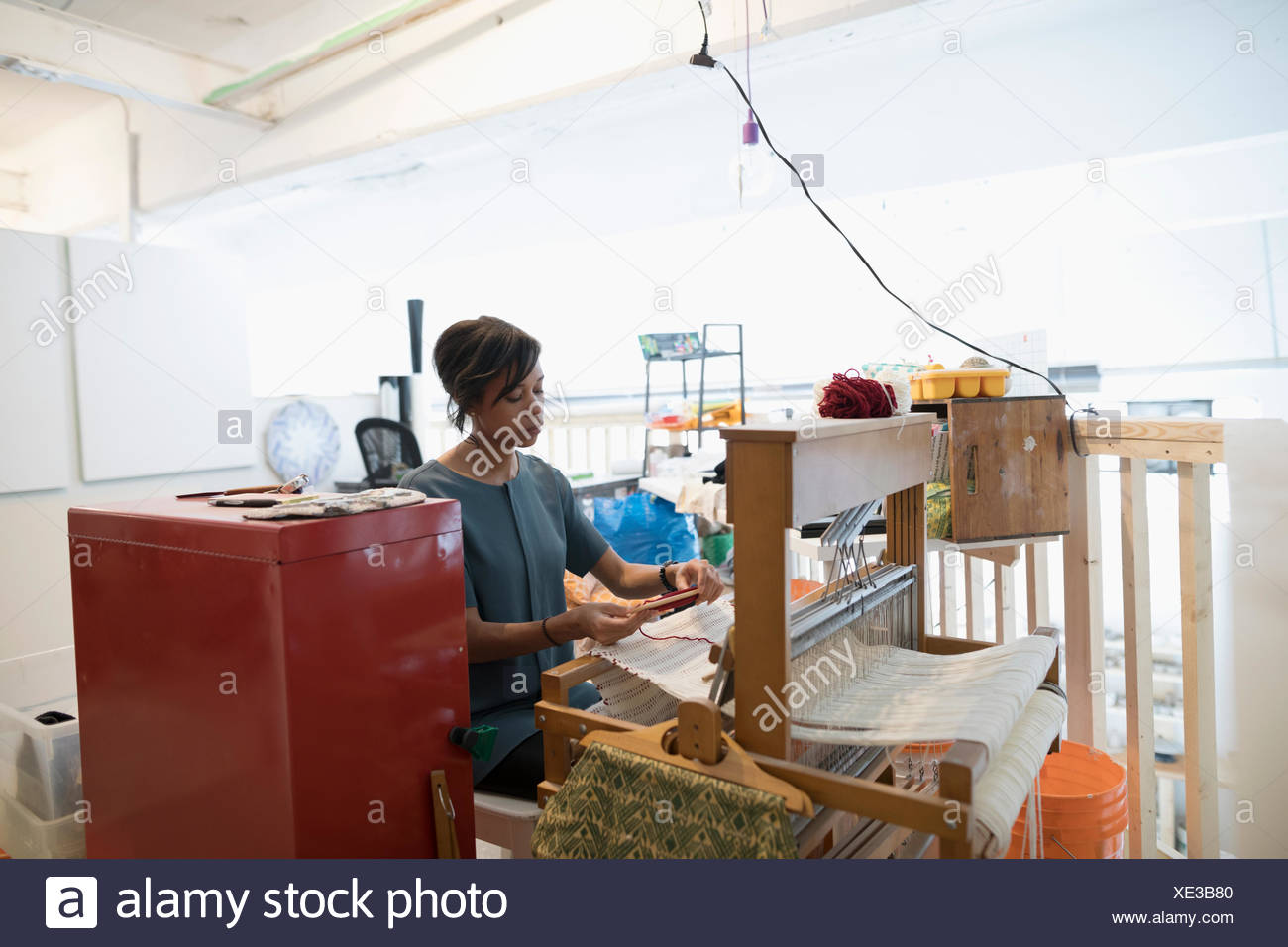 Mujer tejiendo en telar tejedor en art studio Imagen De Stock