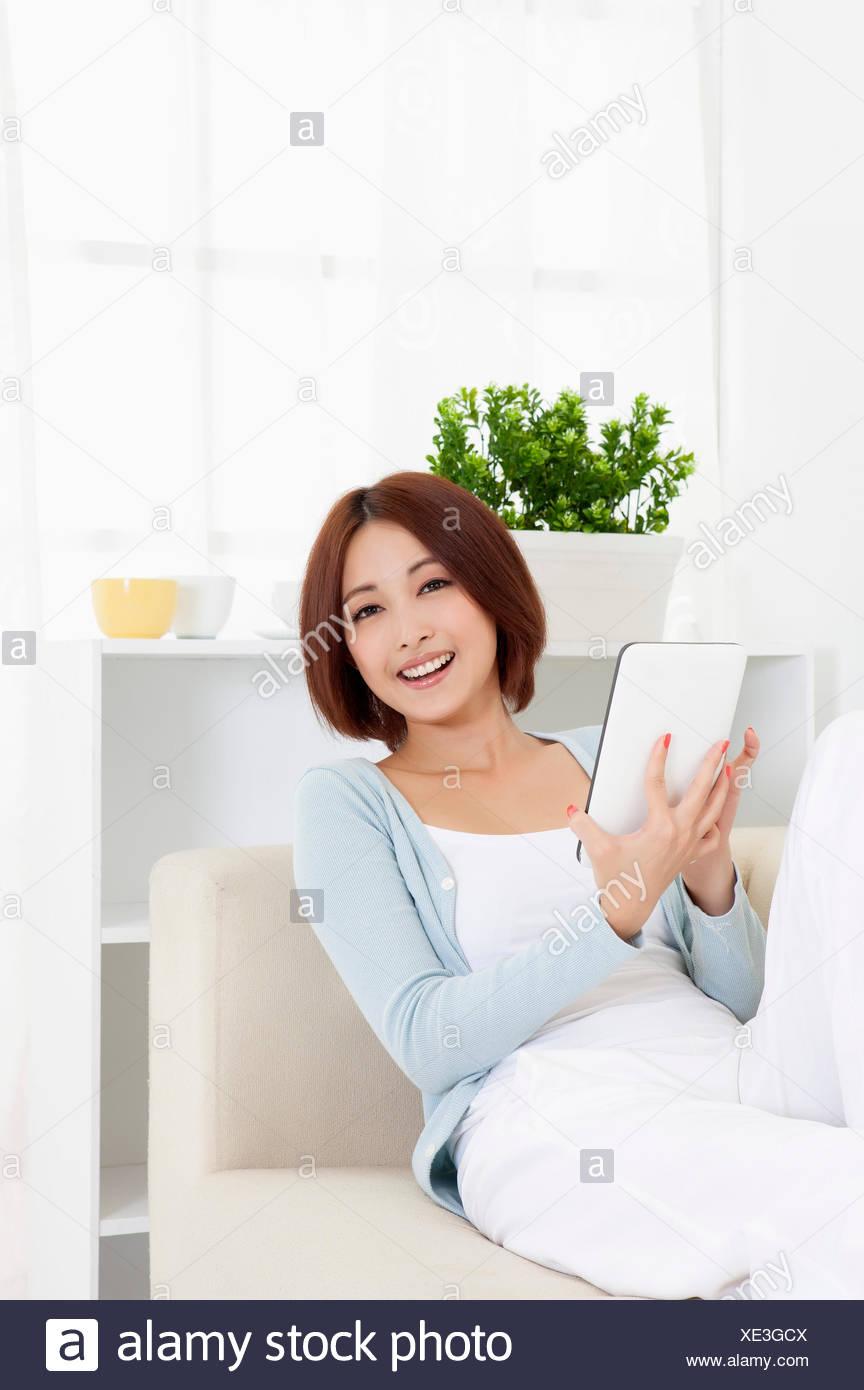Mujer joven sentada y sosteniendo touch pad con sonrisa, Imagen De Stock