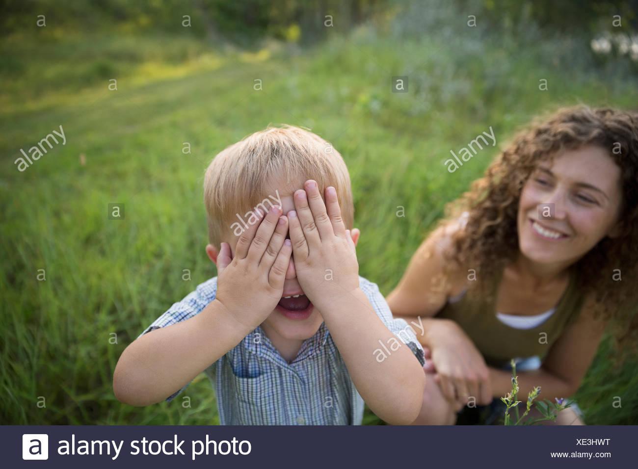 Retrato madre viendo hijo jugando peek-a-boo Imagen De Stock