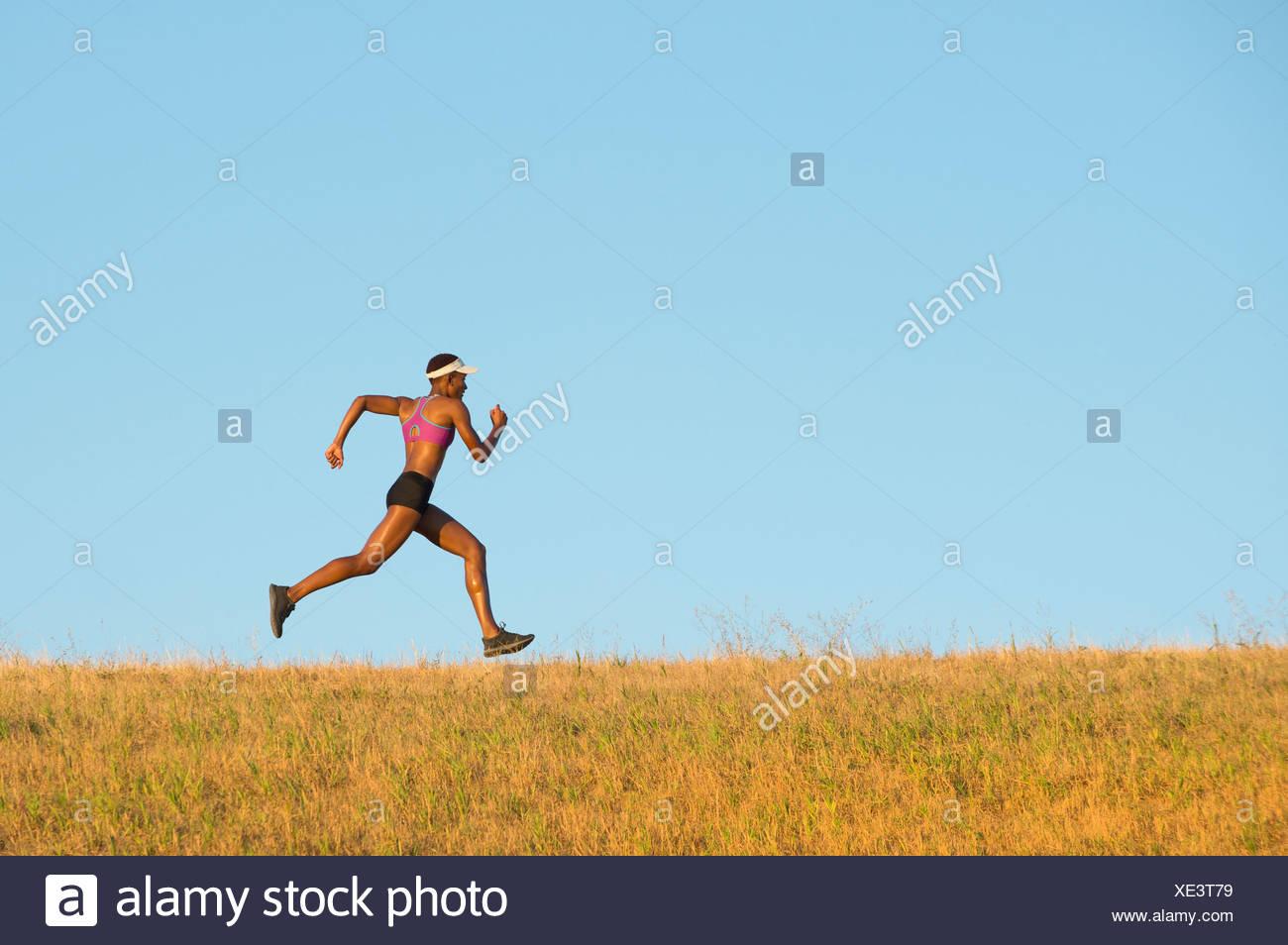 Mujer joven corriendo a través del campo Imagen De Stock