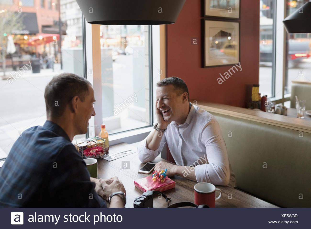 Sonriente pareja homosexual masculina celebrando un cumpleaños en diner booth Imagen De Stock