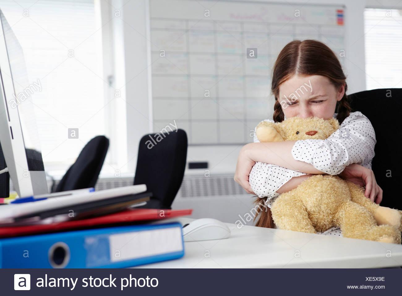 Chica sentada en la oficina abrazando un osito y llorar Imagen De Stock
