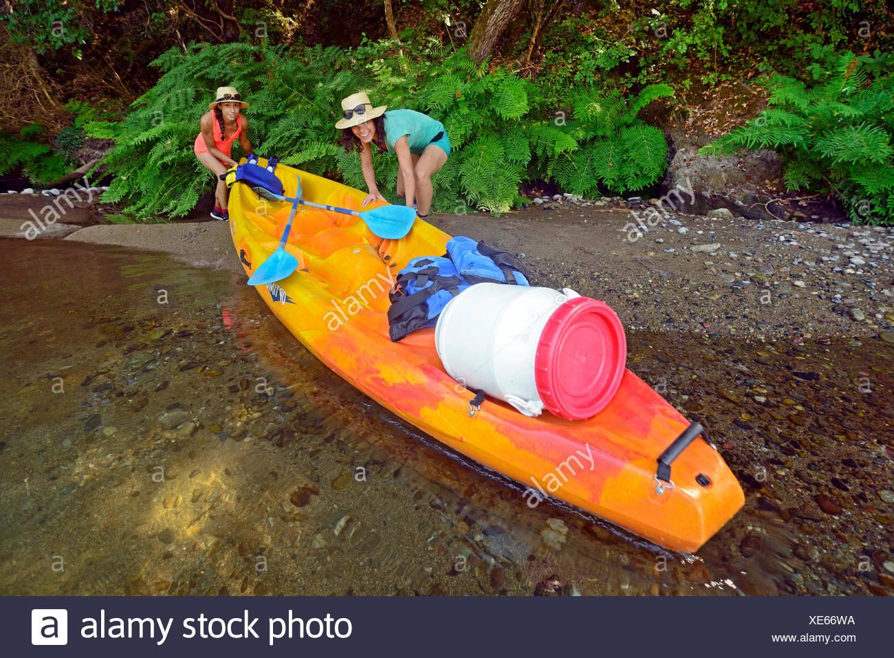 Dos mujeres tirando su kayak del río Golo, Francia, Córcega Bastia Imagen De Stock