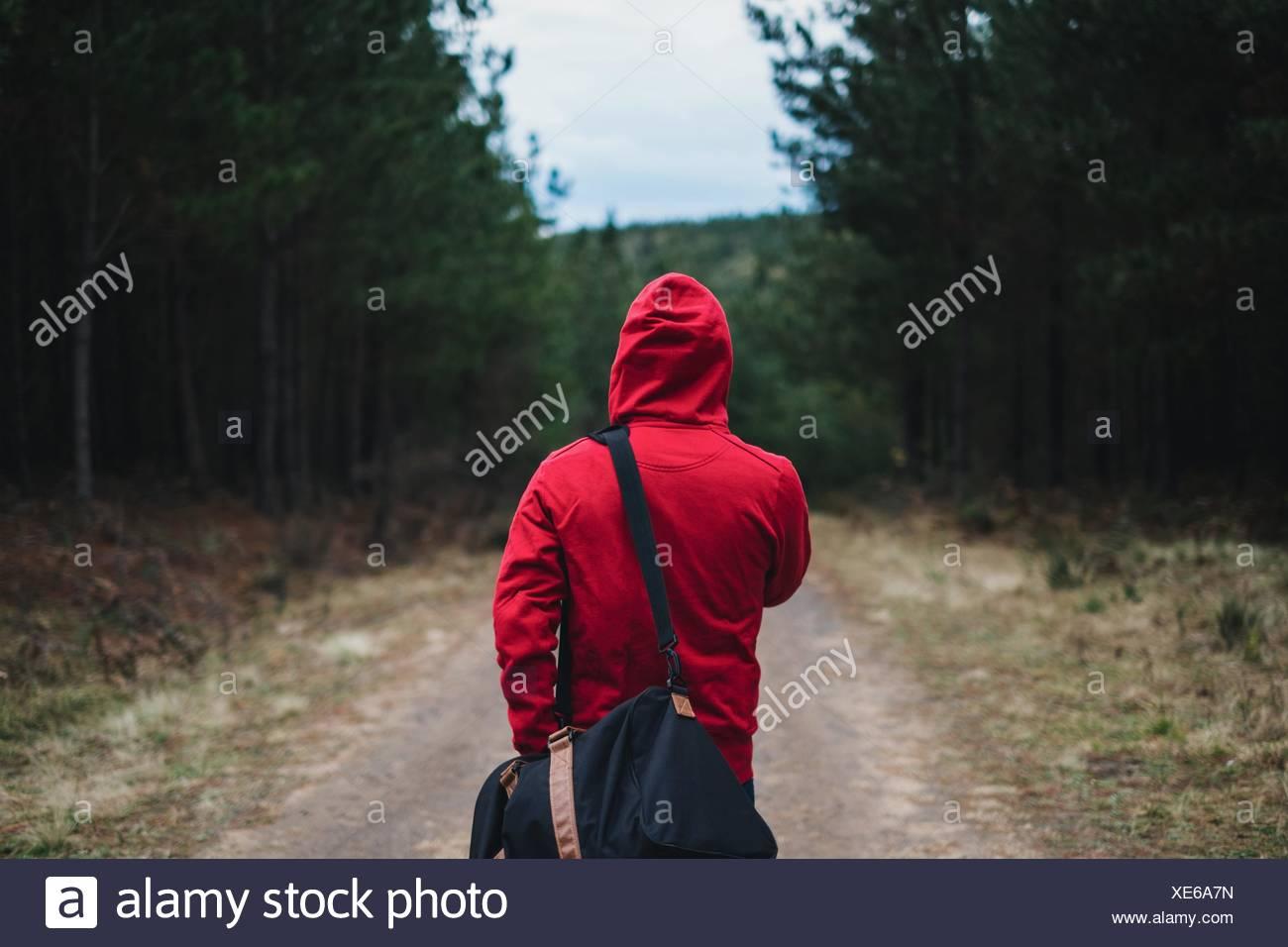 Vista trasera de la persona en Camisa encapuchada caminando con bolsa en Belanglo State Forest Imagen De Stock
