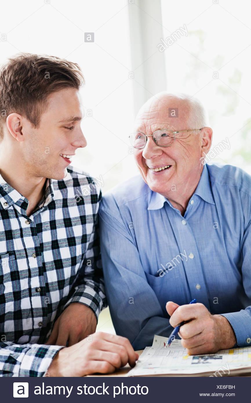 2697cf2f304c3 Feliz el hombre senior y nieto resolver crucigramas Imagen De Stock