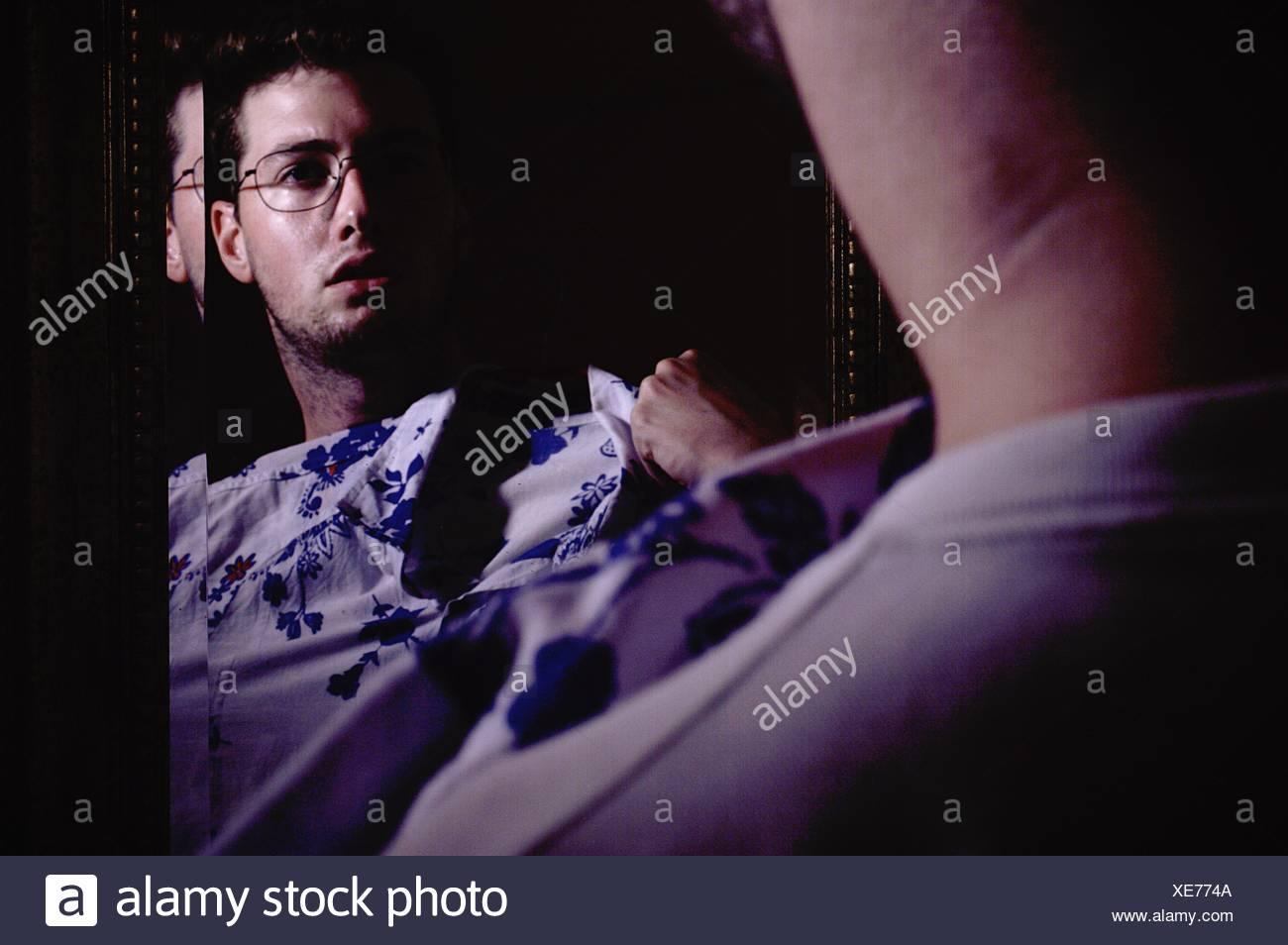 La reflexión del hombre tratando camiseta en espejo Imagen De Stock