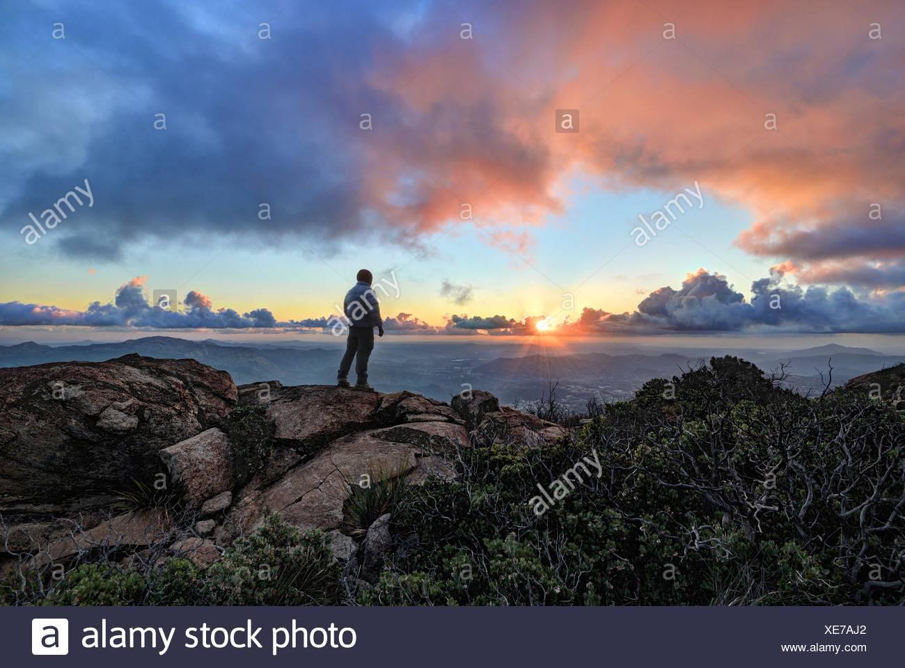 Hombre maduro, de pie sobre una montaña al atardecer, el Bosque Nacional de Cleveland, EE.UU. Foto de stock